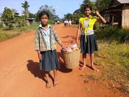 Local girls holding a basket of goods on a village road